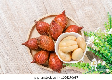 Salak Palm , waive or snake fruit in wooden dish on the table.