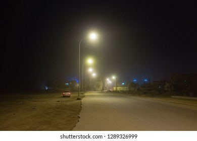 SALALAH, OMAN - AUGUST 21, 2015: A quiet street in the Dahariz district of Salalah at night, with a light sea mist during the 'khareef' monsoon season. Salalah is in the Dhofar province of Oman.