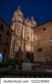 Salamanca, Spain; December 2018: Facade of Casa de las Conchas in Salamanca at night, Spain, covered in scalloped shells, and Salamanca University at illuminated at night. World Heritage Site