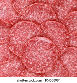 Salami background with many sliced pieces of salami
