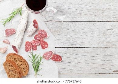 Salami, bread and red wine glass. Meat antipasto platter on wooden table. Top view with copy space