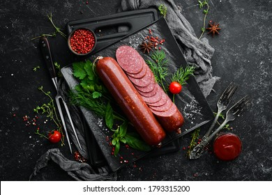 Salami with fresh rosemary and spices. on a black stone background. Top view. Free space for text.