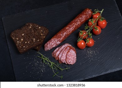 Salami on black stone plate with bread and cherry tomatoes
