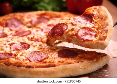 Salami pizza on the table decorated with vegetables and oil