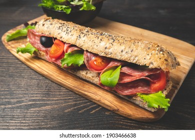 Salami sandwich with multigrain bread baguette with green lettuce and tomato. Takeaway Takeout food. Submarine sandwich top view. Healthy lunch dinner