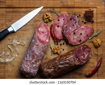 salami sausage, knife, spice and slices of chorizo on chopping board.Top view/Italian sausage.