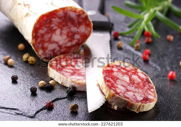 Salami sausage sliced on dark slate background. Selective focus on salami slice.