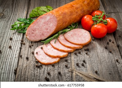 Salami sausages sliced with pepper, garlic and rosemary on cutting board on wooden table.