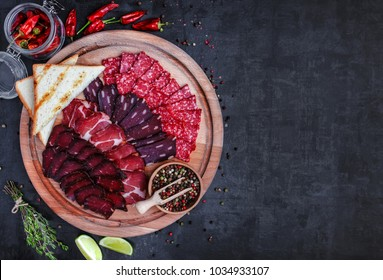 Salami, sliced ham, sausage, prosciutto, bacon. Meat antipasto platter on stone table. Top view with copy space