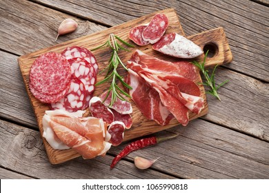Salami, sliced ham, sausage, prosciutto, bacon. Meat antipasto platter on wooden table. Top view