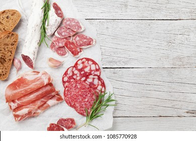 Salami, sliced ham, sausage, prosciutto, bacon. Meat antipasto platter on wooden table. Top view with copy space
