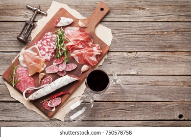 Salami, sliced ham, sausage, prosciutto, bacon. Meat antipasto platter and red wine on wooden table. Top view with copy space