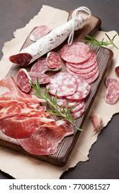Salami, sliced ham, sausage, prosciutto, bacon. Meat antipasto platter on stone table