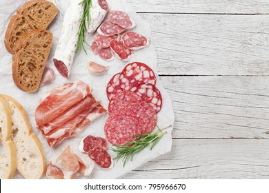 Salami, sliced ham, sausage, prosciutto, bacon, toasts, olives. Meat antipasto platter on wooden table. Top view with space for your text