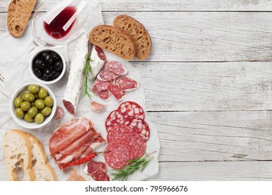 Salami, sliced ham, sausage, prosciutto, bacon, toasts, olives. Meat antipasto platter and red wine on wooden table. Top view with copy space