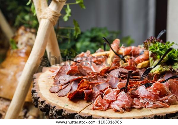 Salami, sliced ham, sausage, prosciutto, bacon. Meat antipasto platter on stone table.