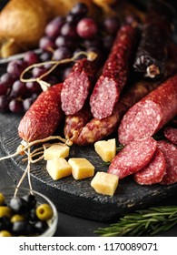 Salami sliced in rustic style. Salami sausage. Different sausages with cheese, grapes and olive.