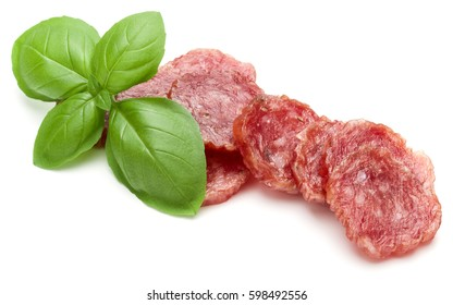 Salami smoked sausage slices and basil leaves isolated on white background cutout.