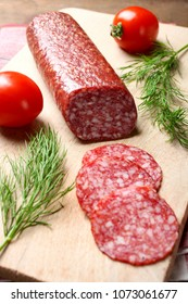 Salami with tomatoes and dill on a cutting board on a black background.