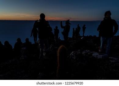 SALAR DE UYUNI, BOLIVIA - APRIL 17, 2015: Tourists watch sunrise on Isla Incahuasi (Isla del Pescado) in Salar de Uyuni salt flat, Bolivia