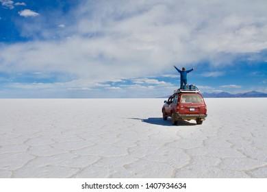 SALAR DE UYUNI, BOLIVIA - AUGUST 2011: man standing on the roof of an off-road vehicle in the Salar de Uyuni the largest salt lake in the world, Bolivia
