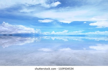 Salar de Uyuni in Bolivia covered with water with clouds reflections soft focus.