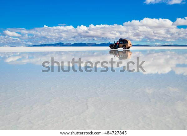 Salar de Uyuni in Bolivia covered with water with car and clouds reflections soft focus