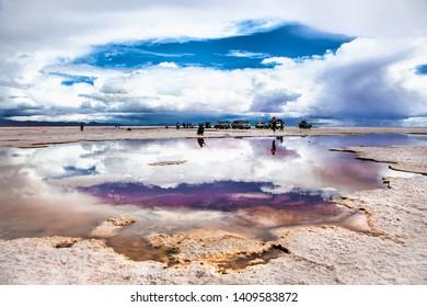 Salar de Uyuni, Bolivia - Dec, 31, 2018: Salar de Uyuni in Bolivia covered with water with car and people reflections