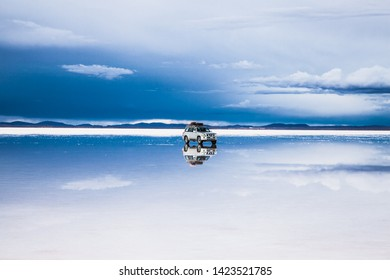 Salar de Uyuni, Bolivia - Dec, 31, 2018: Salar de Uyuni in Bolivia covered with water with car and clouds reflections soft