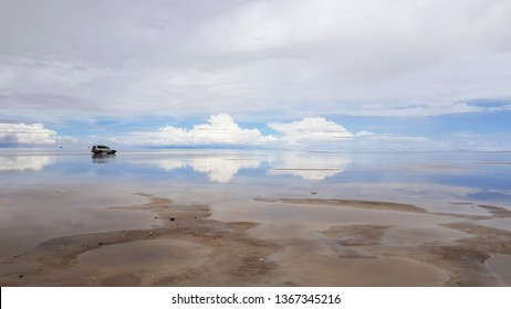 Salar de Uyuni, Bolivia - February, 2019. A car in the Salar de Uyuni flooded after the rains, Bolivia. Clouds reflected in the water of the Salar de Uyuni, Bolivia