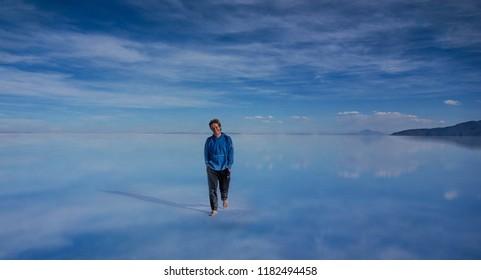 Salar de Uyuni, Bolivia- March 25, 2017: Man walking on the lake Salar de Uyuni, Bolivia