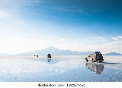 Salar de Uyuni, Bolivia - March, 26, 2017: Off-road cars driving through Salar de Uyuni salt flat in Bolivia