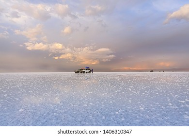SALAR DE UYUNI, BOLIVIA - MARCH, 28,  2019: The tour group and car are in Salar de Uyuni at sunset. Beautiful clouds in the sunset light. In the foreground salt outgrowths in shallow water.