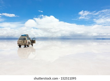 SALAR DE UYUNI - JANUARY 14: Off-road car on reflected surface of lake Salar de Uyuni in Bolivia on January 14, 2013. Salar de Uyuni is the world's largest salt flat at 10,582 square kilometers