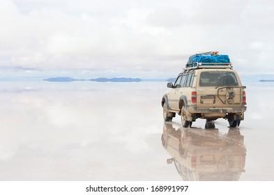 SALAR DE UYUNI - JANUARY 14: Off-road car moving on reflected surface of lake Salar de Uyuni in Bolivia on January 14, 2013. Salar de Uyuni is the world's largest salt flat at 10582 square kilometers