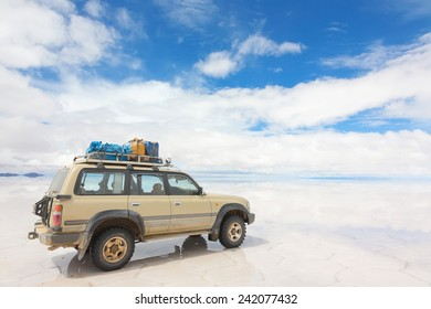 SALAR DE UYUNI - JANUARY 14: Off-road car on the reflected surface of lake Salar de Uyuni in Bolivia on January 14, 2013. Salar de Uyuni is the world's largest salt flat at 10582 square kilometers
