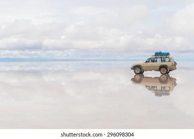 SALAR DE UYUNI - JANUARY 14: Off-road car moving on the reflected surface of lake Salar de Uyuni in Bolivia on January 14, 2013. Salar de Uyuni is the world's largest salt flat at 10582 square km.
