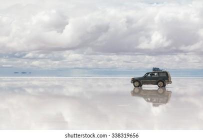 SALAR DE UYUNI - JANUARY 14, 2013: Off-road car moving on reflected surface of lake Salar de Uyuni in Bolivia on January 14, 2013. Salar de Uyuni is the world's largest salt flat at 10582 square km