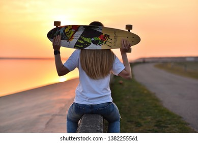 Salaspils, Latvia - April 22 2019: A young blonde girl sitting with a longboard on a stone fence by a reservoir lake on the Daugava river. Spring. Orange sunset. Still water.