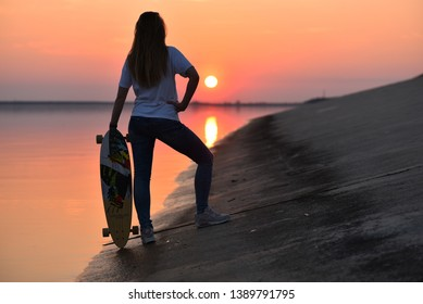 Salaspils, Latvia - April 22 2019: A girl with a longboard watching an orange sunset over the reservoir lake on the Daugava river. Still water. Spring.