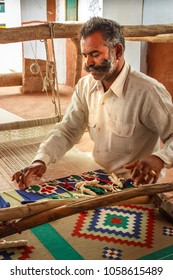 Salawas, Rajasthan/India - April 3, 2009: Mustached man weaving  a diamond-patterned Dhurrie rug on a horizontal loom
