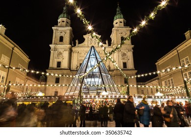 SALBURG, AUSTRIA - 11TH DECEMBER 2015: Decorations and buildings at Salzburg Christmas Market in the Domplatz area at night. People can be seen.