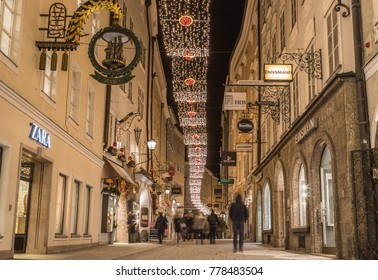 SALBURG, AUSTRIA - 20TH DECEMBER 2017: A view along Getreidegasse in Salzburg at night during the Christmas season. Decorations, people, shops and buildings can be seen.