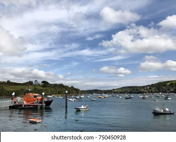 Salcombe Harbour, West Hams, Devon, United Kingdom. 29th August 2017. Salcombe harbour with the RNLI lifeboat with small sailing craft, ribs and speed boats on the water on a cloudy blue sky day.
