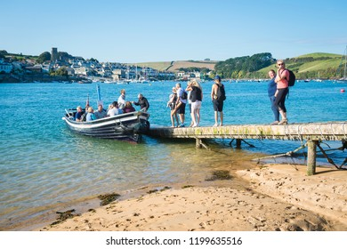 SALCOMBE, UK - SEPTEMBER 27, 2018: Passengers board a small ferry boat on the beach to cross the harbor to the popular seaside resort town.