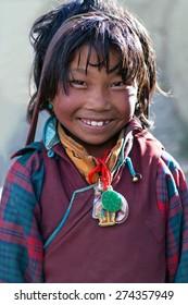 SALDANG, NEPAL - SEPTEMBER 06: Smiling Tibetan girl from the village of refugees poses for the photo during her break timel on September 06, 2011 in Saldang, Upper Dolpo, Nepal