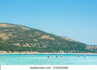 Salde lake, Turkey-August 2019 Beach with white sand and blue water against the background of mountains and blue sky. People relax on the beach.