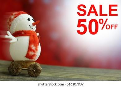 Sale 50% Christmas and New Year`s background with snowmen slides down on holiday bokeh lights. Foreground ready for product montage.Concept market banner, advertising poster with copyspace.