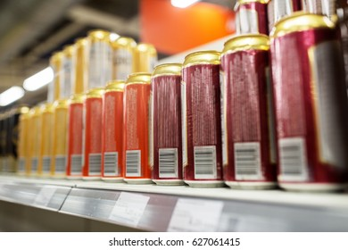 sale and alcohol concept - close up of beer or cider cans at liquor store