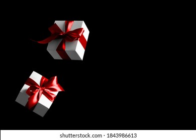 Sale background black. White gifts with red bow falling on dark background for Black Friday banner. Flying backdrop with space for text.